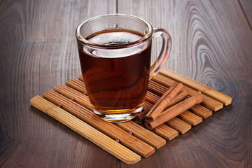 teacup with hot tea and cinnamon sticks