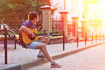 Young hipster man sitting during sunshine with acoustic guitar w