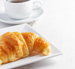 Cup of coffee and croissant on white wooden table