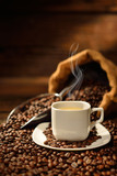 Fototapeta Kawa jest smaczna - Coffee cup with smoke and coffee beans on old wooden table © amenic181