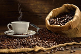 Fototapety Coffee cup with smoke and coffee beans on old wooden table