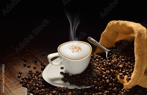 Cup of coffee with smoke and coffee beans on old wooden table