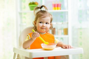smiling kid eating food on kitchen