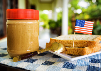 Jar of peanut butter and toasts with flag of USA on summer terra