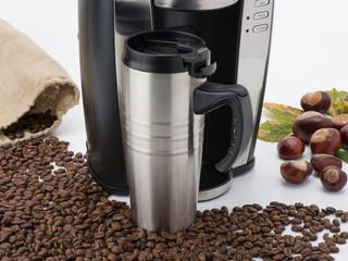 Kaffeemaschine mit Thermobecher, Kaffeebohnen und Kastanien