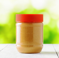Jar of peanut butter on nature background