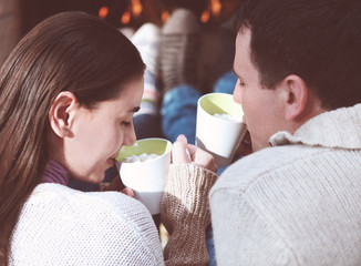 Couple holding cups with hot chocolate with marshmallows
