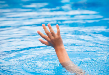 Hand of drowning person stretching out of water .
