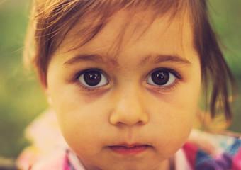 vintage closeup portrait of Cute sad kid with big eyes