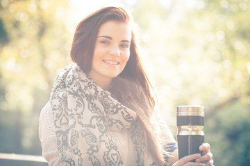 Woman with thermos outdoor portrait in sunny daylight