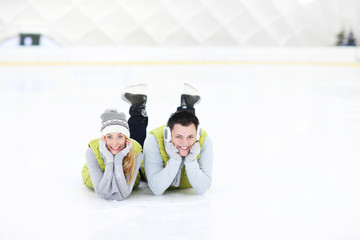 Cheerful couple lying on the skating rink