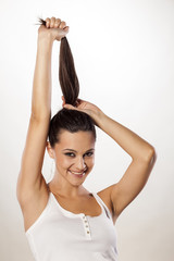 Happy attractive girl holding her hair in a ponytail