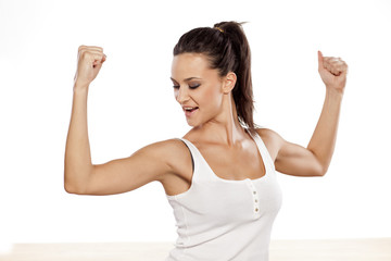 Happy attractive girl showing her biceps