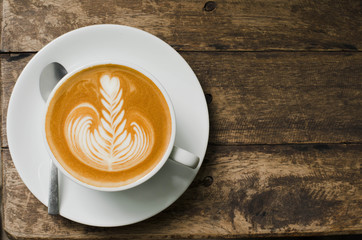classic foamy cappuccino on dark grained wood table from above