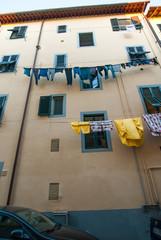 Finestre e bucato di panni lavati stesi, vestiti appesi