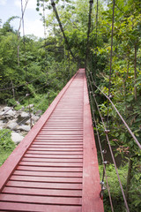 Red wooden suspension bridge over the stream, Thailand
