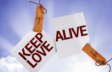 Keep Love Alive on Paper Note on sky background