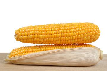 ripe ears of corn on a wooden plank