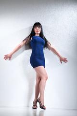 Sexy Frau mit langen schwarzen Haaren lehnt an Wand