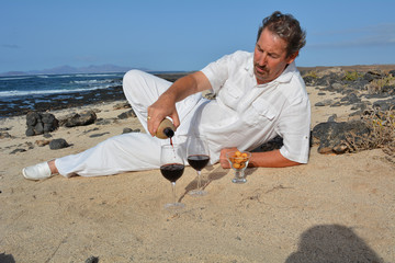 Man pouring red wine from bottle into a glass on the beach