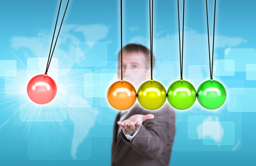 Businessman in suit hold Newtons cradle
