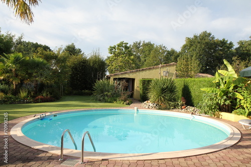 Leinwanddruck Bild jardin exotique et piscine circulaire
