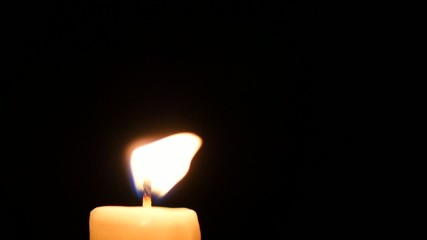 Close-up of a candle flame on black background. Loop.