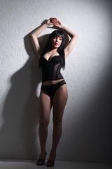 Hübsche junge Frau in Dessous lehnt sexy an Wand