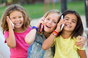 Group of childrens using mobile phones in the park.