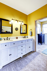 Beautiful  vanity cabinet in bright yellow bathroom