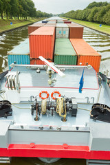 Ship carrying containers on canal