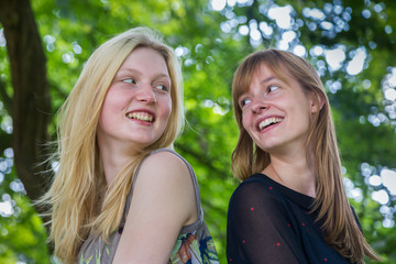 Two caucasian girls with long hair laughing to each other
