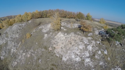 Aerial view. Flying over the rocky hill, autumn landscape.