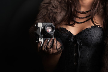 woman wearing corset and fur and holding vintage camera