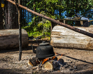 kettle hanging over the fire in the forest