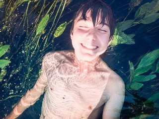 Young boy submerged in a pure river