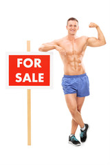 Handsome man standing by a for sale sign