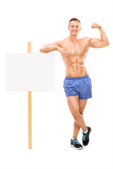 Muscular man standing by a banner and showing bicep