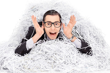 Terrified man covered in a pile of shredder paper