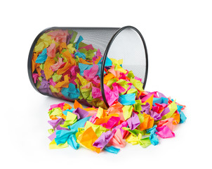 Trash with colored paper on white background.