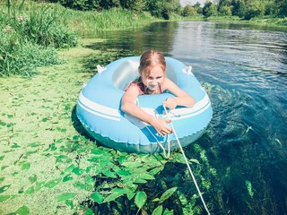 Little girl resting in a raft on a river