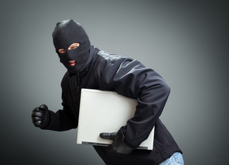 Thief stealing laptop computer