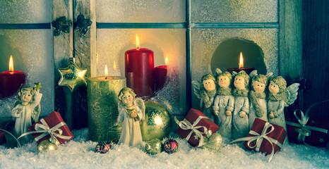 Weihnachtsdekoration mit Engel, Kerzen und Schnee im Fenster
