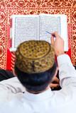 Asian Muslim man studying Koran or Quran