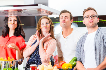 Freunde kochen Pasta und Fleisch zuhause in Küche