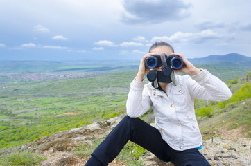 Girl sitting on rock and looking with binocular