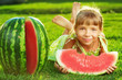 Cute little girl eating watermelon and lying on the green grass