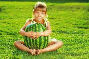 Happy little girl is hugging huge watermelon sitting on a lawn