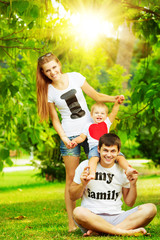 Happy young family having fun in the green summer park outdoors