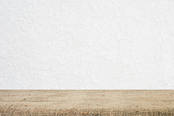 Sackcloth over table and white cement wall, background, template